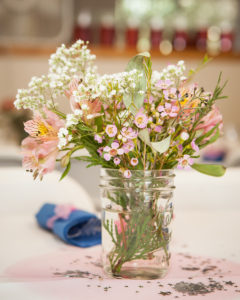pink and white wild flowers placed in a mason jar